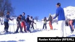 Арстанбаптык балдарга америкалык туристтер лыжа тебүүнү үйрөтүүдө