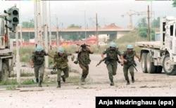 Українські та французькі миротворці ООН ховаються від снайперського вогню в центрі боснійської столиці Сараєво під час осади та обстрілів міста військами боснійських сербів. 21 липня 1994 року
