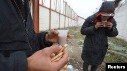 Disa migrantë duke u ushqyer në një fabrikë të braktisur, afër kufirit të Serbisë me Kroacinë.