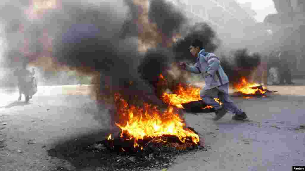 An Afghan boy runs next to fire during a protest in Jalalabad on February 22.