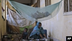 A displaced Pakistani child sleeps in a hammock as her mother, accompanied by another child, cleans items after fleeing their flood-hit homes in September 2011.
