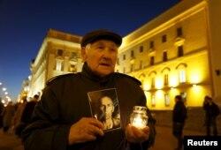 86-гадовы Ўладзімер трымае сьвечку з партрэтам свайго бацькі — ахвяры сталінскіх рэпрэсій