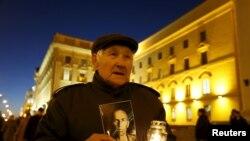 86-річний Володимир тримає свічку з портретом свого батька – жертви сталінських репресій, Мінськ, 29 жовтня 2015