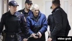 Юрий Дмитриев в окружении полицейских