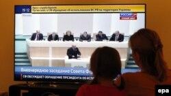 Женщина с ребенком у телевизора во время трансляции заседания Совета Федерации, где рассматривают вопрос использования армии за пределами России.