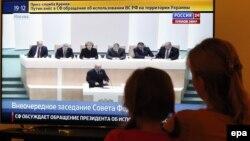 Ресей парламентінің президент Владимир Путиннің Украина территориясында әскер пайдалану туралы ұсынысын талқылауын көріп отырған азаматтар. Ресей, 1 наурыз 2014.