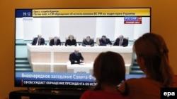Женщина с ребенком смотрят телевизор во время обсуждения в парламенте России вопроса об использовании вооруженных сил на территории Украины. 1 марта 2014 года.