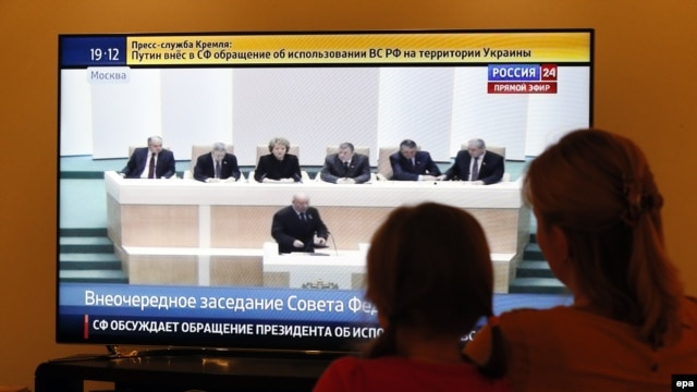 A woman and her daughter watch television during a discussion on the proposal of Russian President Vladimir Putin and the use of Russian armed forces in Ukraine in parliament in Moscow on March 1.