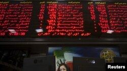 An official works at her desk in the main hall of the Tehran Stock Exchange in early August.