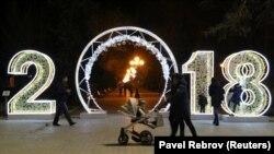 Люди прогуливаются мимо праздничной инсталляции в курортной Евпатории, 28 декабря 2017 года