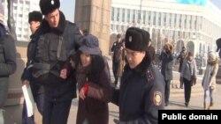 Блогер Дина Байділдаеваны (ортада) полиция алаңнан әкетіп барады. Алматы, 8 ақпан 2014 жыл.