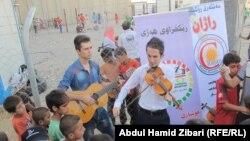 العازف نوروز ناظم مع زميله برفقة نازحين