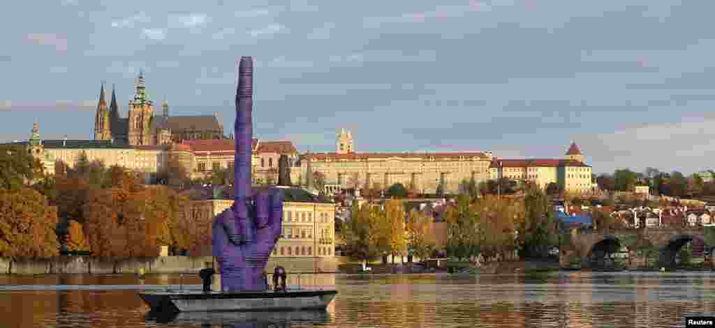 Workers anchor a boat bearing a controversial installation work by Czech visual artist David Cerny in front of Prague Castle in Prague on October 21. (Reuters)