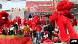 Huge red bears and other soft toys are prominently displayed for sale by a vendor on Valentine's Day in Baghdad.