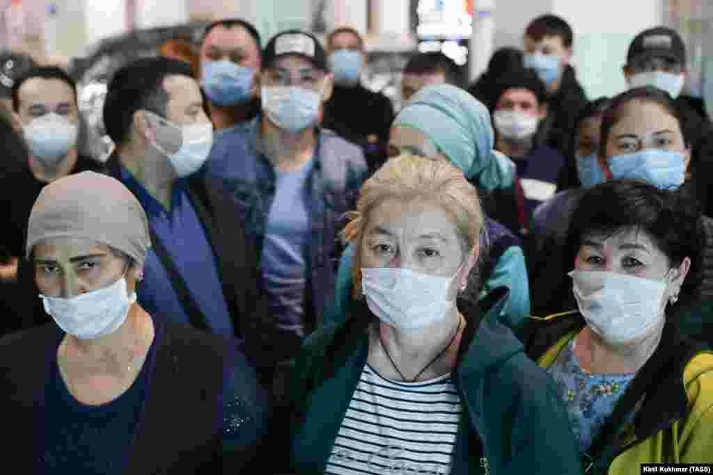 Workers from Kyrgyzstan wear face masks on March 30 as they wait to find out how the can leave Tolmachevo International Airport in Novosibirsk. They do not appear to be practicing physical distancing to prevent the spread of the coronavirus.