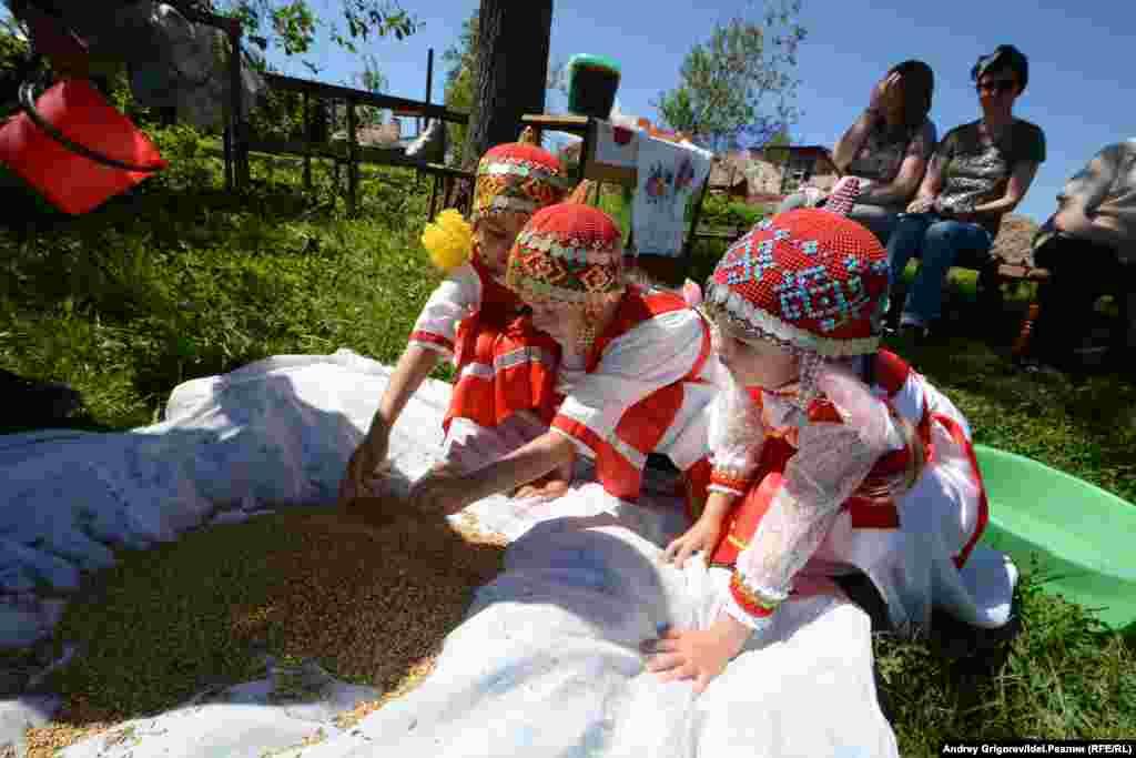Младшее поколение тоже здесь: три девочки в красивых национальных нарядах внимательно наблюдают за происходящим. Когда-нибудь и они будут варить традиционное чувашское пиво.