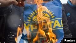 """Члены оппозиционной ОСДП на акции протеста против результатов выборов сжигают плакат партии """"Нур Отан"""" и бюллетени. Алматы, 17 января 2012 года."""