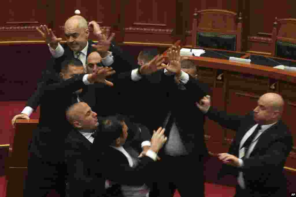 Security hold opposition lawmaker Endri Hasa (foreground center) as he throws an egg at Albanian Prime Minister Edi Rama (background left) during a debate in parliament in Tirana on December 20. (AP)