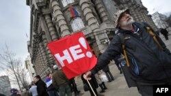 Un protestatar în fața sediului guvernului la Belgrad