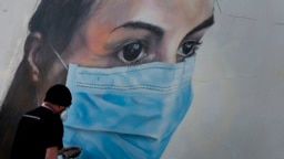 BELGIUM -- Graffiti artist Bram De Ceurt works on a street graffiti piece of a nurse with a mouth mask to protect against coronavirus in Antwerp, Belgium, Thursday, March 26, 2020.