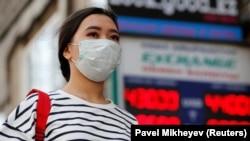 Женщина в защитной маске на фоне табло с курсами покупки и продажи валют частного обменного пункта. Алматы, 16 марта 2020 года.