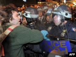 A protester is confronted by New York police officers as authorities cleared Zuccotti Park.