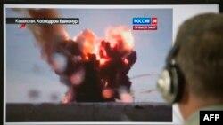 """2 шілде 2013 жылы """"Протон-М"""" зымыран тасығышының Байқоңырдан ұша бере апатқа ұшыраған сәтін Ресейдің """"Россия 24"""" телеарнасының тікелей эфир хабарынан көріп отырған адам. (Көрнекі сурет)"""