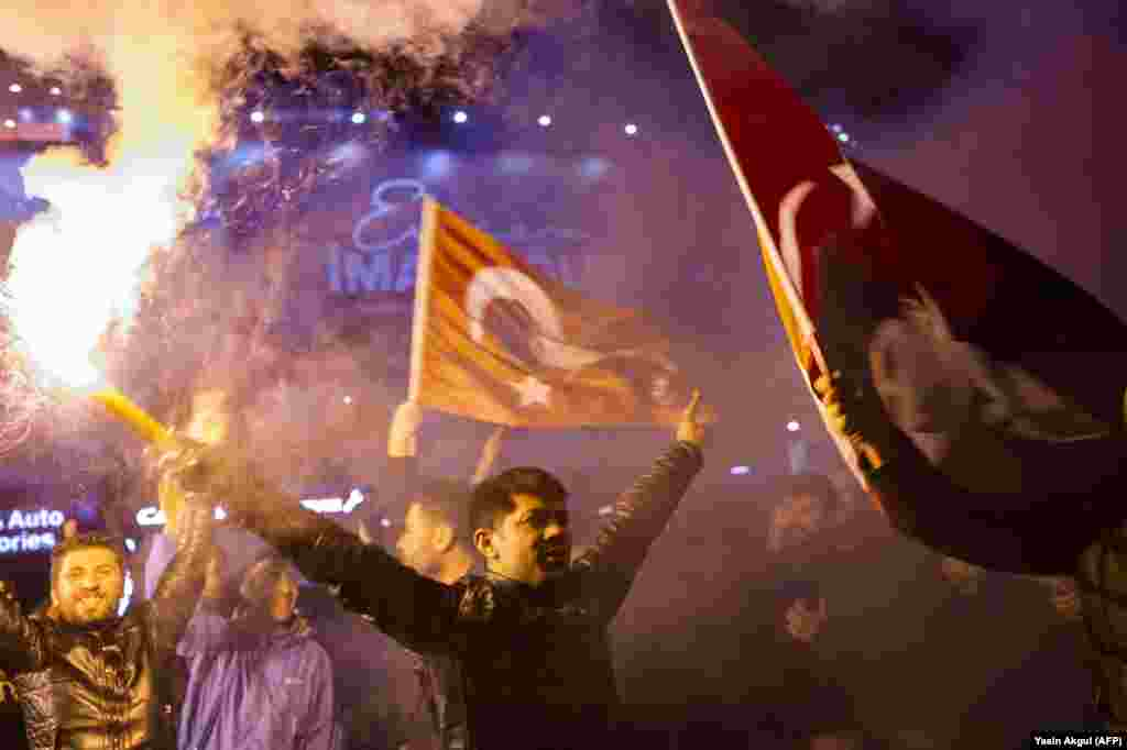 Supporters of the main opposition Republican People's Party (CHP) in Turkey wave flags and light torches to celebrate local election results in Istanbul on April 1. (epa-EFE/Martin Divisek)