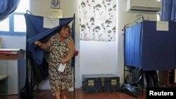 Женщина выходит из кабинки для голосования на референдуме. Афины, 5 июля 2015 года.