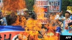 South Korean protesters burn a North Korean flag and portraits of Kim Jong Il in Seoul.