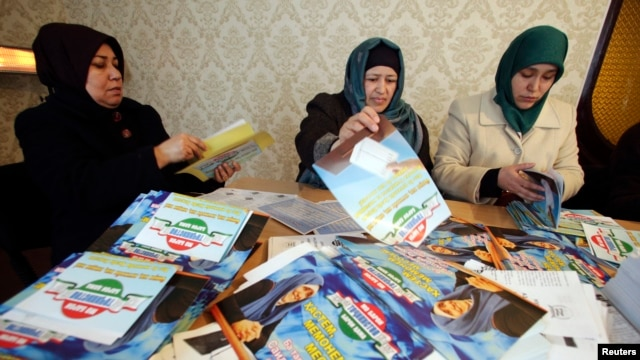 Supporters of the Islamic Renaissance Party of Tajikistan sort preelection leaflets at party headquarters in the capital, Dushanbe, in February.