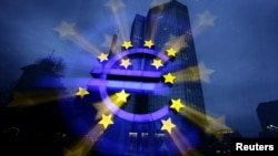 Подсвеченный символ евро у здания Европейского Центробанка во Франкфурте-на-Майне.