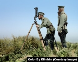 Tsar Nicholas II peering through periscope binoculars near a front line during World War I.