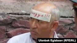 Активист Ондуруш Токтонасыров возле здания суда с требованием освободить Текебаева. 16 августа 2017 года.