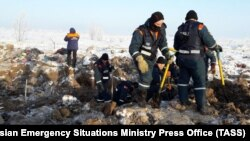 Russian Emergency Situations Ministry employees collect debris at the crash site on February 11.