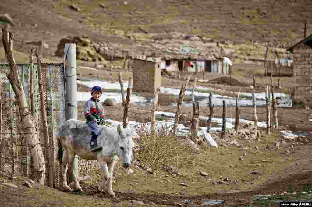 A boy rides a donkey in the village of Deman, near the Iranian border.