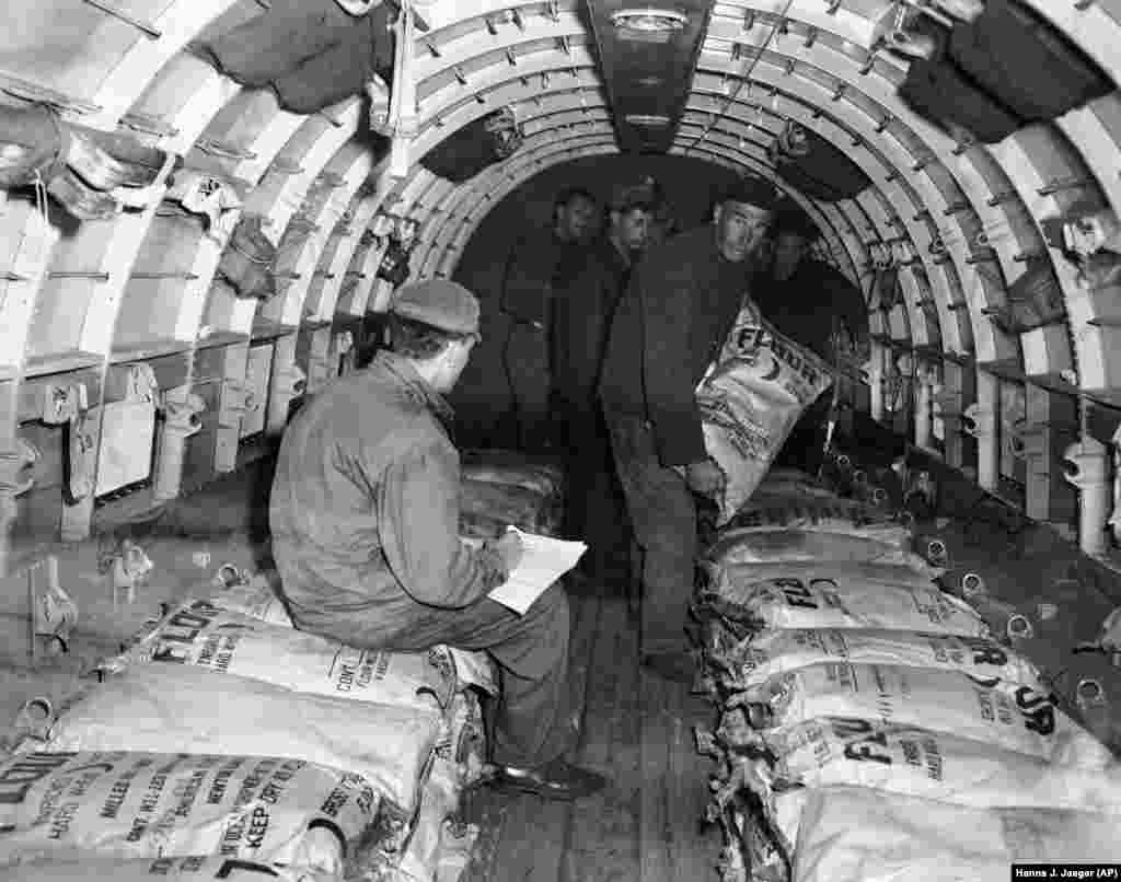 A U.S. soldier checks a manifest while overseeing the loading of flour into a C-47 transport at Frankfurt's Rhein-Main Air Base on June 29, 1948. The base was the main supply hub for the Berlin Airlift.