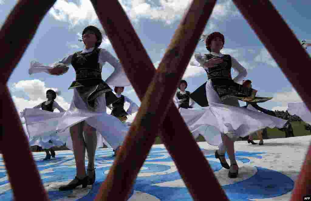 Kyrgyz women wearing traditional costumes perform during a folk festival at Son-Kul Lake, 3,016 meters above sea level, some 350 kilometers from Bishkek. (AFP/ Vyacheslav Oseledko)