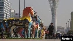 """Астананың орталығындағы """"Бәйтерек"""" монументі жанынан өтіп бара жатқан адамдар. Қыркүйек, 2015 жыл."""