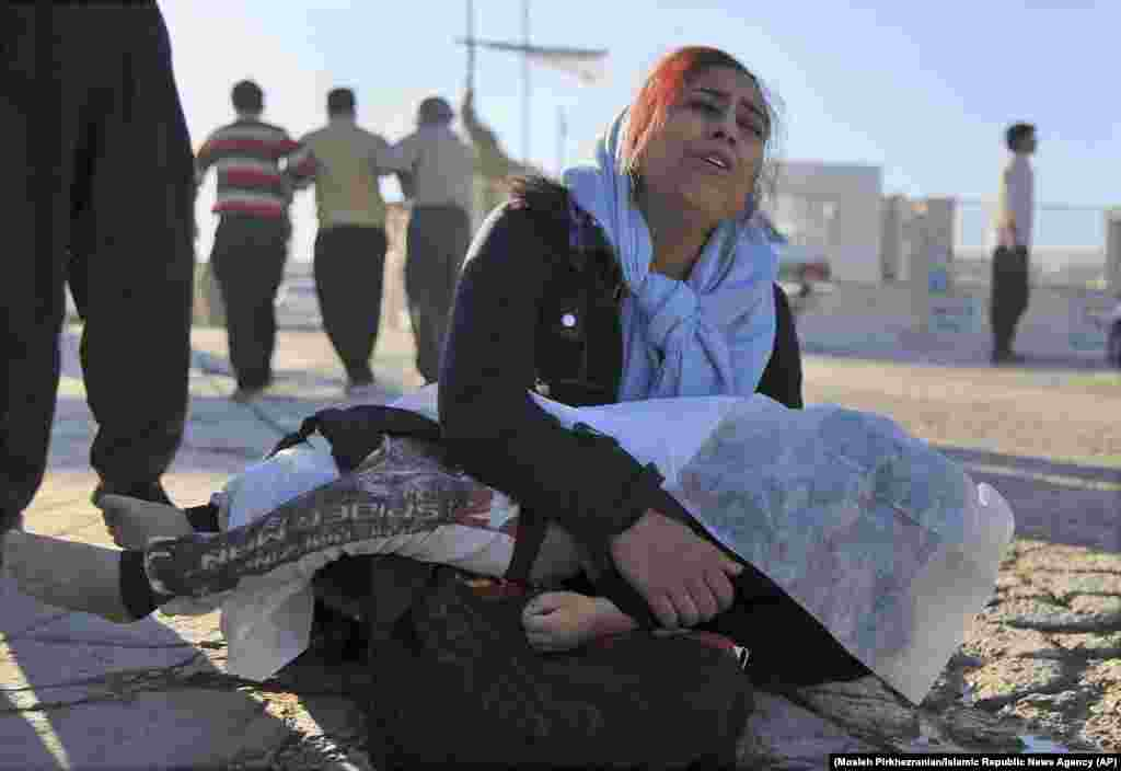 A woman mourns as she holds the body of her daughter in Sarpol-e Zahab.