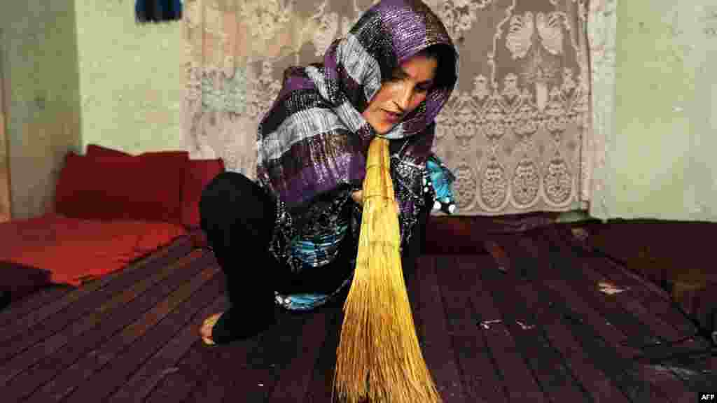 Pari, 33, sweeps her house in the Afghan city of Herat. She lost her hands when she was 7 when her village was bombed during the Soviet invasion. She sells handicrafts to feed her three children and her elderly husband. (AFP/Aref Karimi)