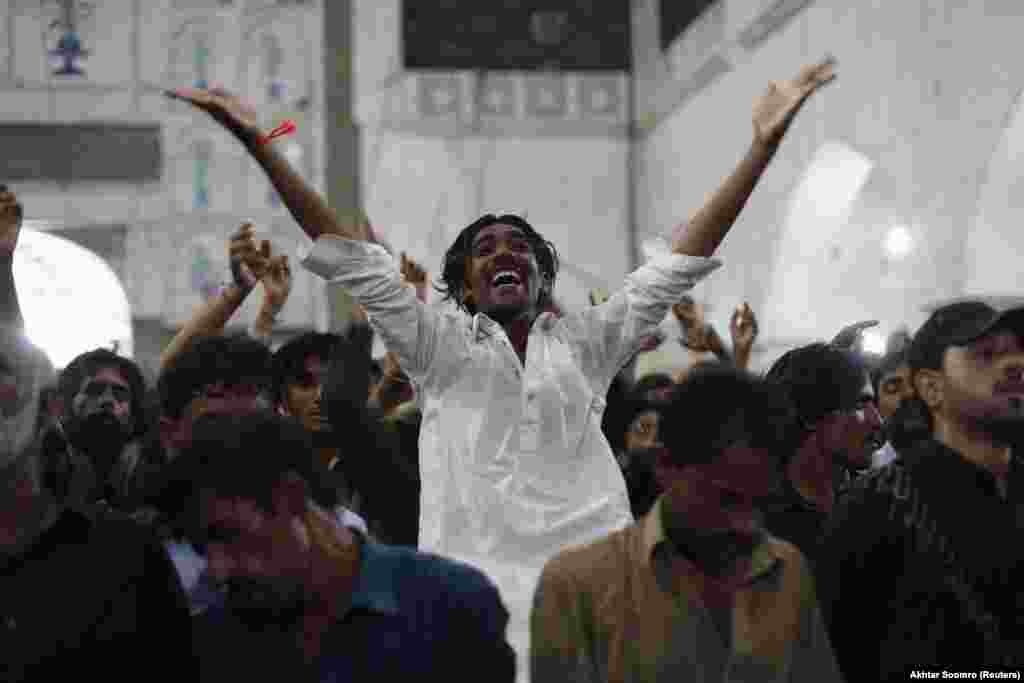 "A devotee dancing to the beat of the drum at the Lal Shahbaz Qalandar shrine in 2013. The Huffington Post describes Sufism as a branch of Islam which ""employs music, dance and spiritual recitation to awaken the God who Sufis say is asleep in the human heart."""