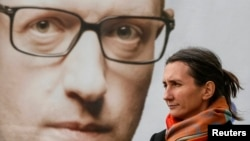 In Kyiv, a woman stands in front of a campaign poster with a portrait of Ukrainian Prime Minister Arseniy Yatsenyuk.
