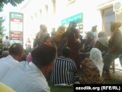Люди стоят в очереди перед зданием филиала банка Ипак йули в городе Андижане, чтобы получить денежный перевод.