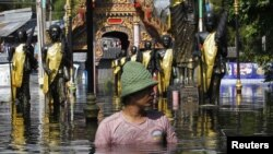 Thailand -- A man wades through a flooded temple in Don Muang district in Bangkok, 27Oct2011