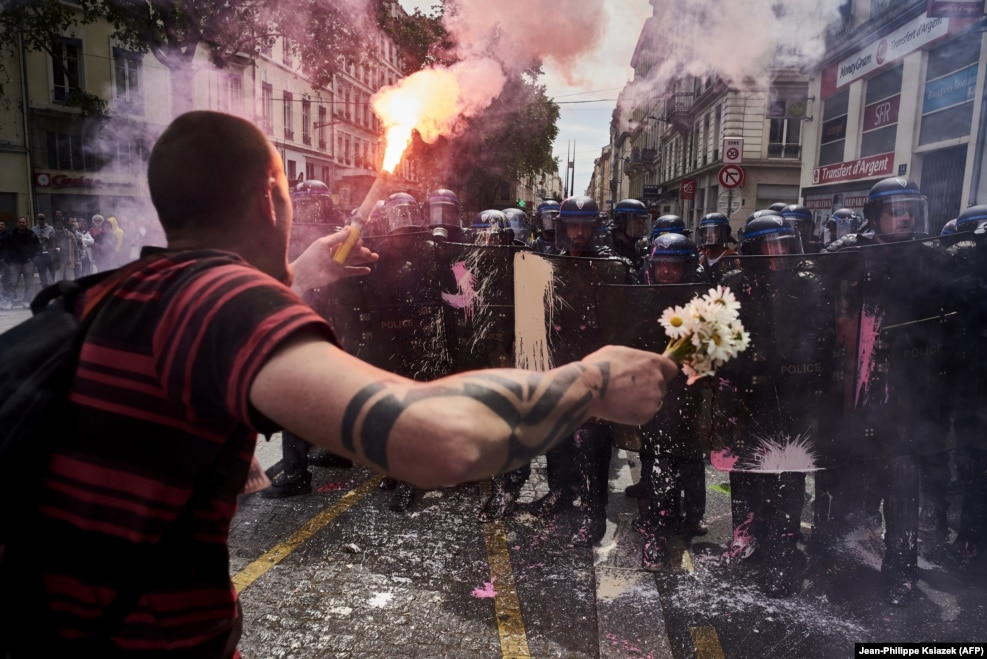 """When France was rocked by violent protests against a change to France's labor laws, AFP's Jean-Philippe Ksiazek donned a gas mask and helmet to cover protests in Lyon in May. As rocks and paint flew, the seasoned news photographer noticed a bouquet of flowers on the ground that some young female demonstrators had dropped. """"I bent down to photograph the flowers, then this guy with huge hands picked the flowers up from in front of my camera. Then I stood up and took this photo of him.... We [photographers] are always proud to take a photo that endures a little. We take so many pictures and they are usually forgotten."""" Despite the unrest France's government pushed ahead with the controversial labor legislation, making it easier foremployersto hire and fire."""