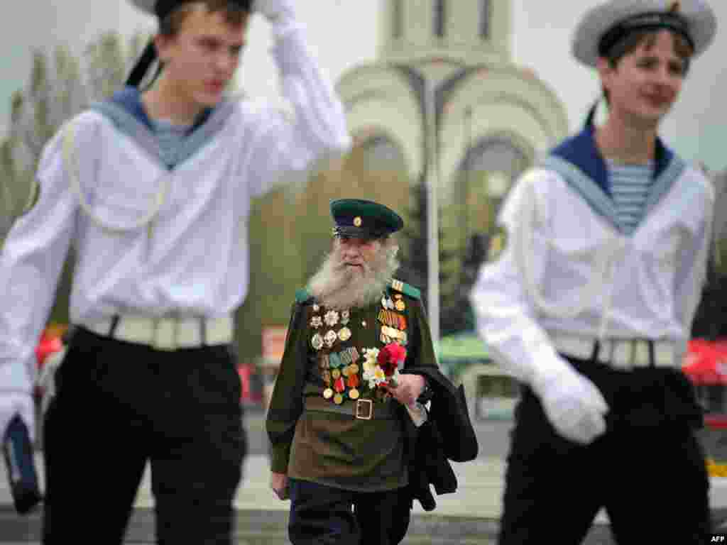 A Russian World War II veteran follows naval cadets at a war memorial in Moscow ahead of the country's Victory Day on May 9 Photo by Alexander Nemenov for AFP.