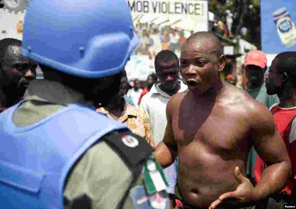A former Liberian soldier shouts in front of a Nigerian UN peacekeeper during an antigovernment demonstration concerning wage arrears in Monrovia in February 2007.