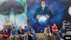 Activists sit near graffiti depicting Russian President Vladimir Putin at the summer camp of the pro-Kremlin youth group Nashi at Lake Seliger this past summer.