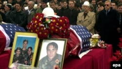 People pay their last respects in February 2002 to the three Bytyqi brothers -- Ylli, Agron, and Mehmet -- who were found the previous June in a grave with more than 70 other Kosovo Albanians in Serbia's Petrovo Selo.